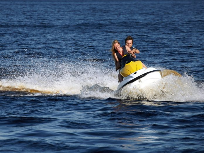 Happy couple riding a jet ski in the ocean