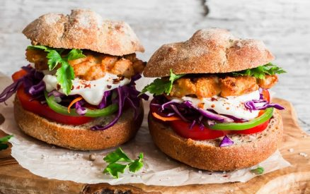 Homemade fish burger on a light rustic wooden board