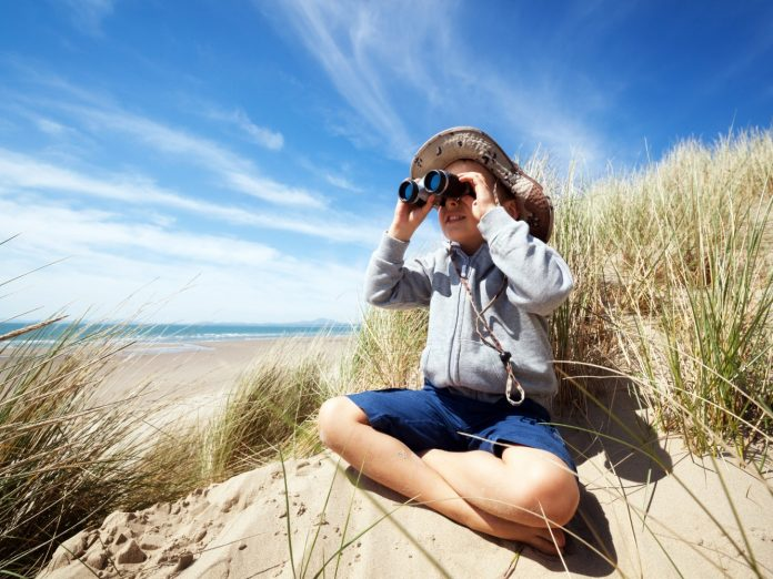 Little boy searching with binoculars at the beach on an eco tour on the isle of palms