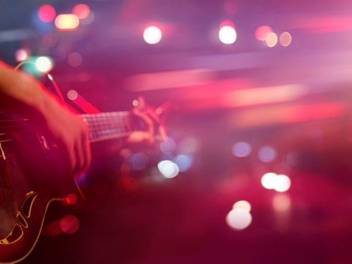 a musician playing a guitar at a bar