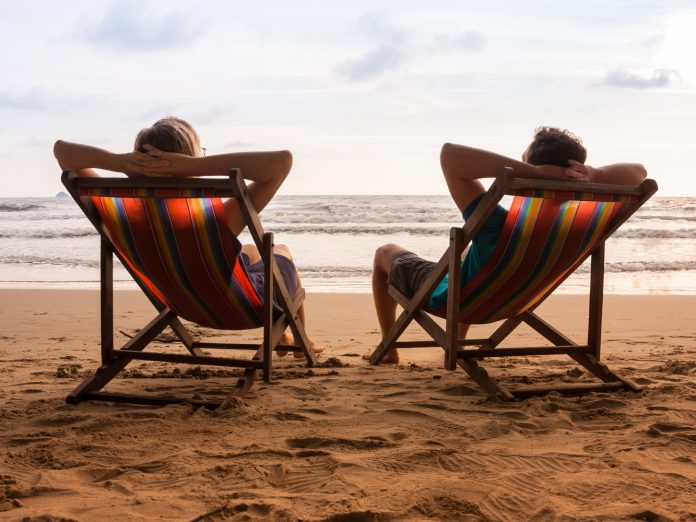 Romantic couple sitting in deck chairs thinking about kiawah island vs. isle of palms