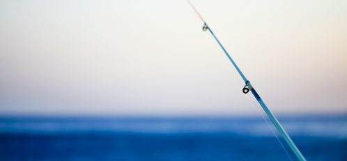 fishing pole in front of the ocean; surf fishing on Isle of Palms