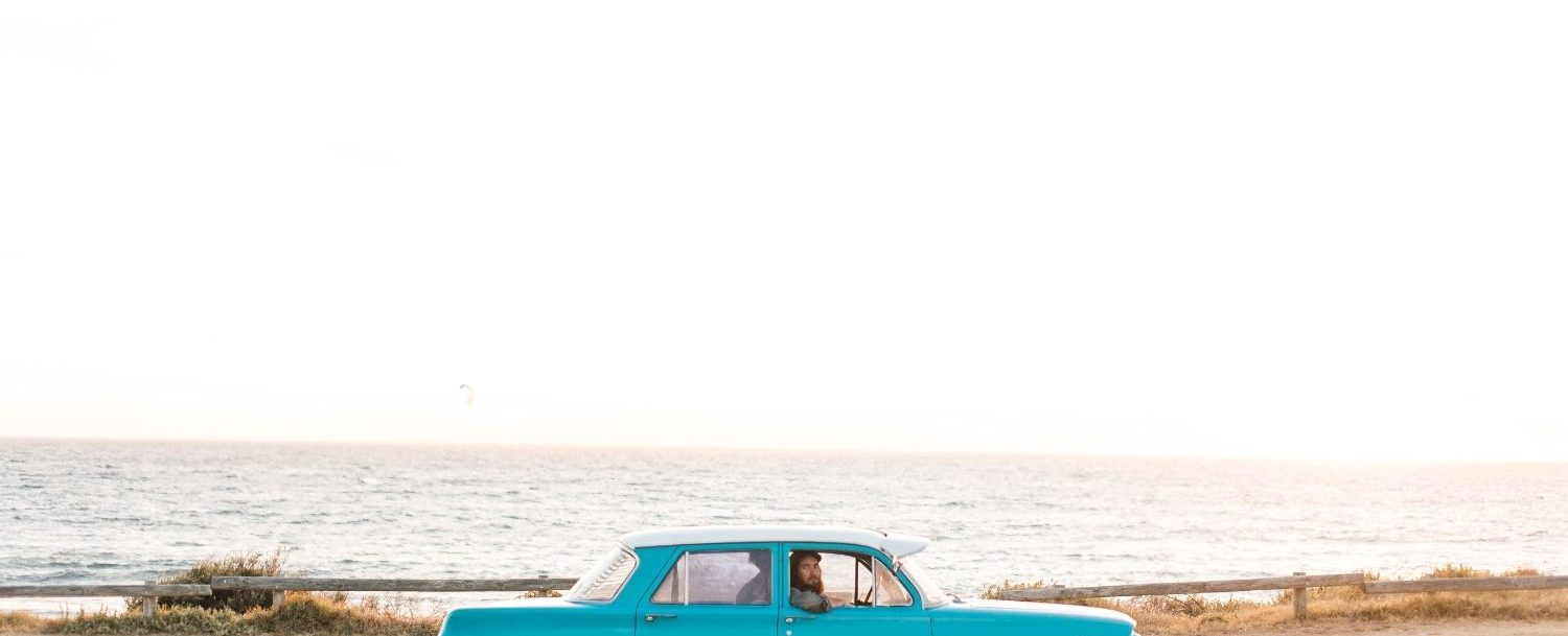 Vintage car driving along the coast