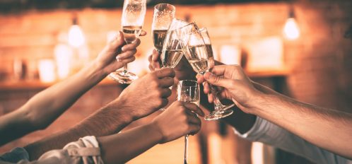 Group of people cheering with champagne flutes with home interior in the background
