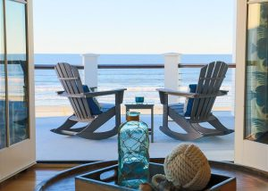 two beach chairs on a deck overlooking the ocean