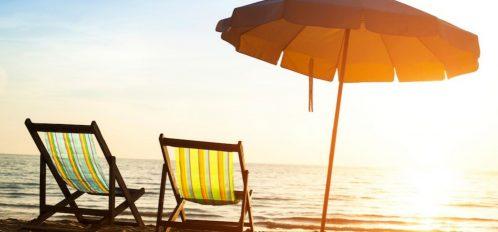 Beach chairs and an umbrella on the beach during sunrise