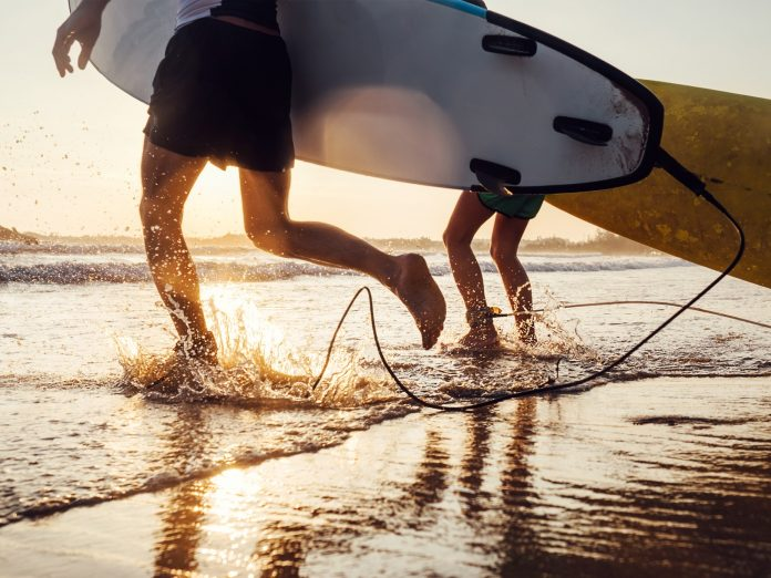 two people with surfboards running into the ocean