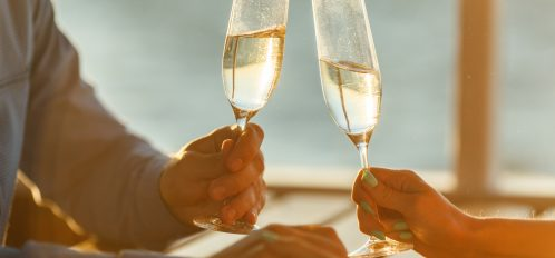 Man and woman holding champagne glasses with water view