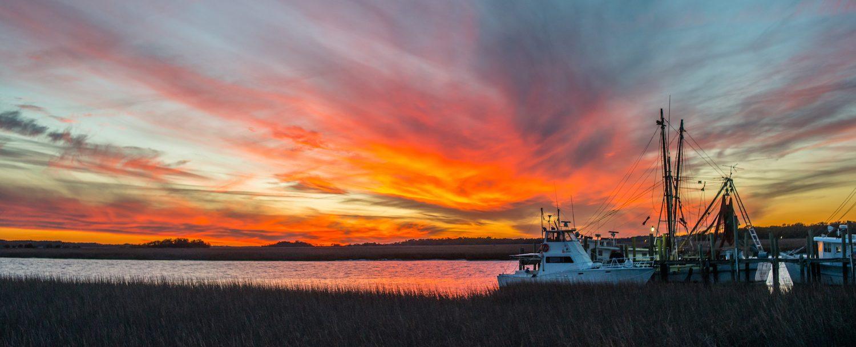 Boat on Isle of Palms marina at sunset.