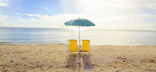 Two chairs on the beach.