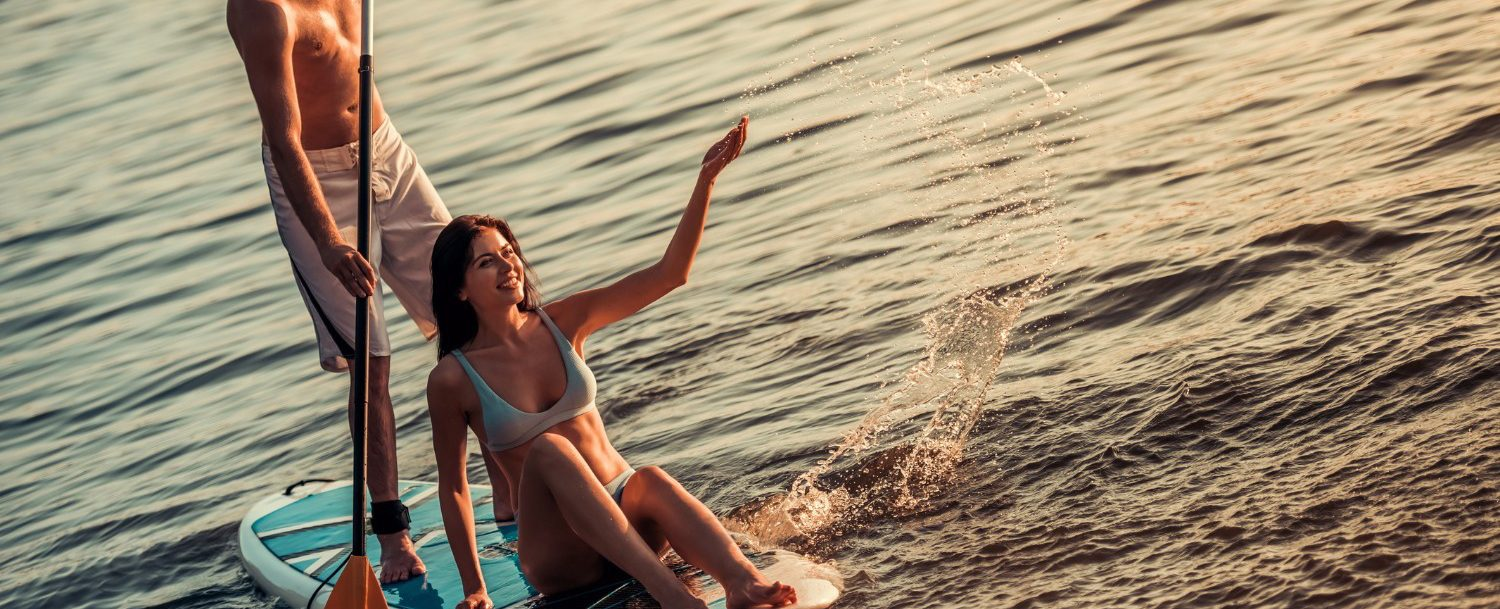 Beautiful young couple is talking and smiling while SUP surfing on the river