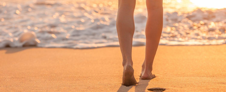 Closeup of woman's feet walking down a tropical sandy beach at sunset.
