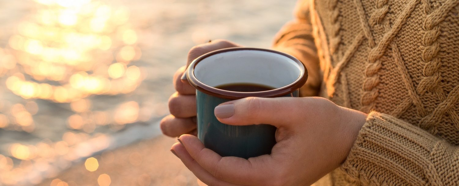 Closeup shot of female hands in cozy sweater holding dark green mug with tea at sunset light with beautiful golden bokeh (Closeup shot of female hands in cozy sweater holding dark green mug with tea at sunset light with beautiful golden bokeh, ASCII,