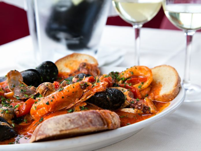 Horizontal sea food tomatoes mediterranean soup with bread and glass of white wine