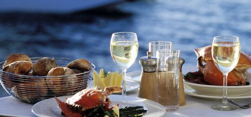 Table of food near the water. Waterfront dining.