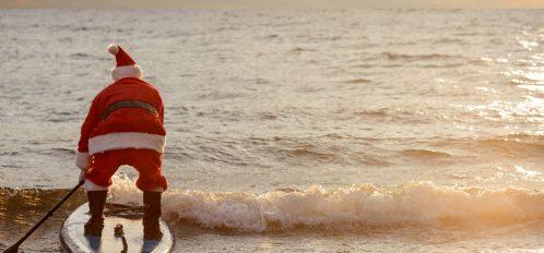 Santa surfing in the ocean.