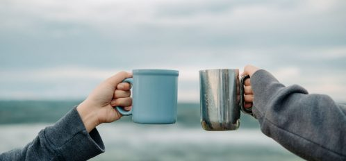 Two people holding coffee cups in front of the ocean.
